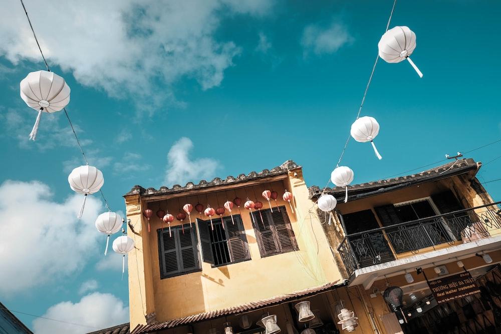 white paper lanterns hanged near beige concrete house