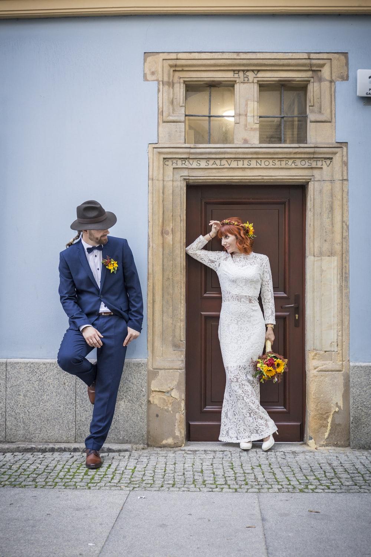 man leaning back on wall beside woman standing beside closed door