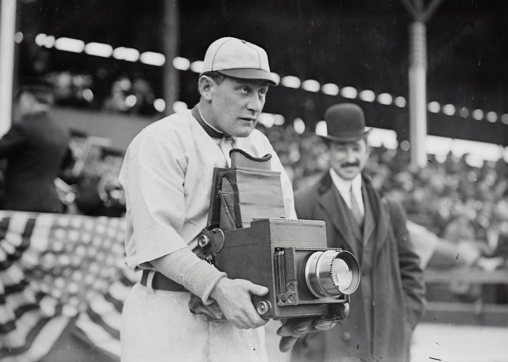 Germany Schaefer, Washington AL (baseball) holding a photographer's camera