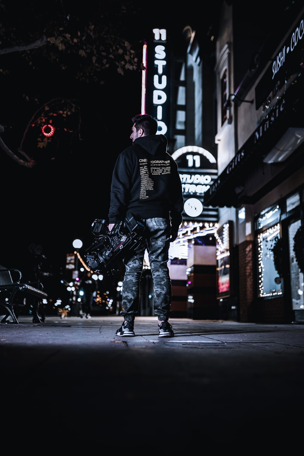 low-angle photography of man standing outside a building during nighttime