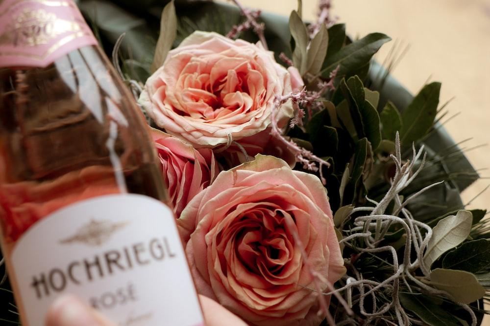 Hochriegl rose bottle beside white rose flowers