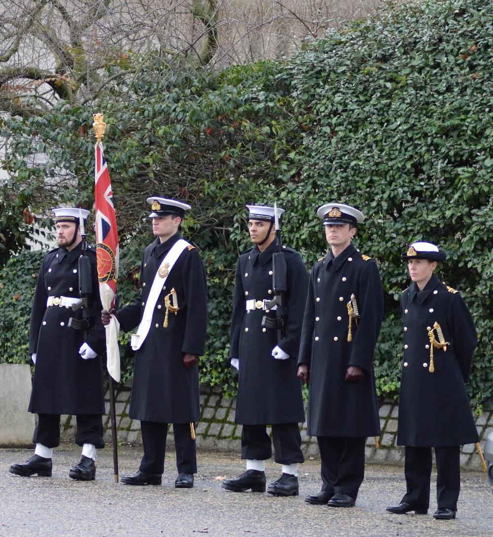 five men wearing soldier coats during daytime