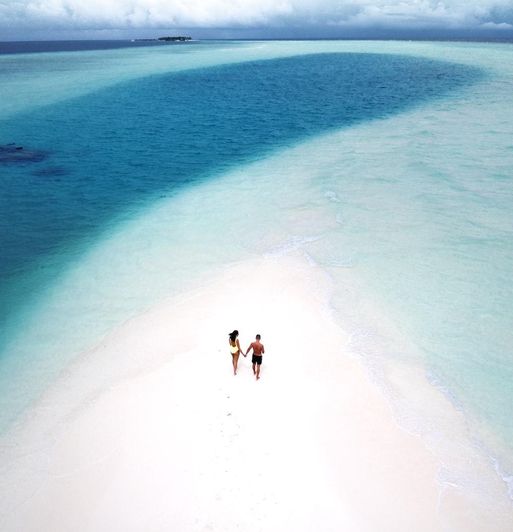 two person walking on sandbar