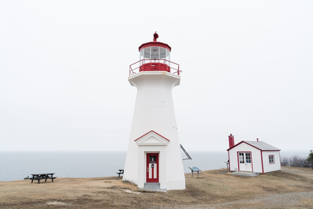 white lighthouse near shed