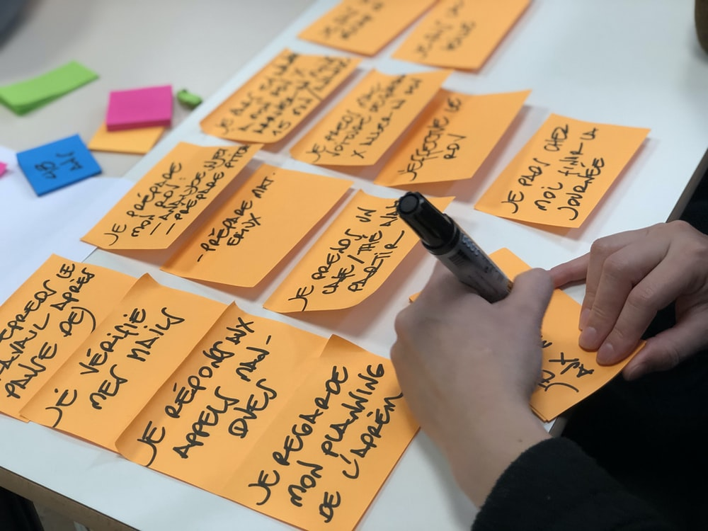 shallow focus photo of person writing on orange paper sheet