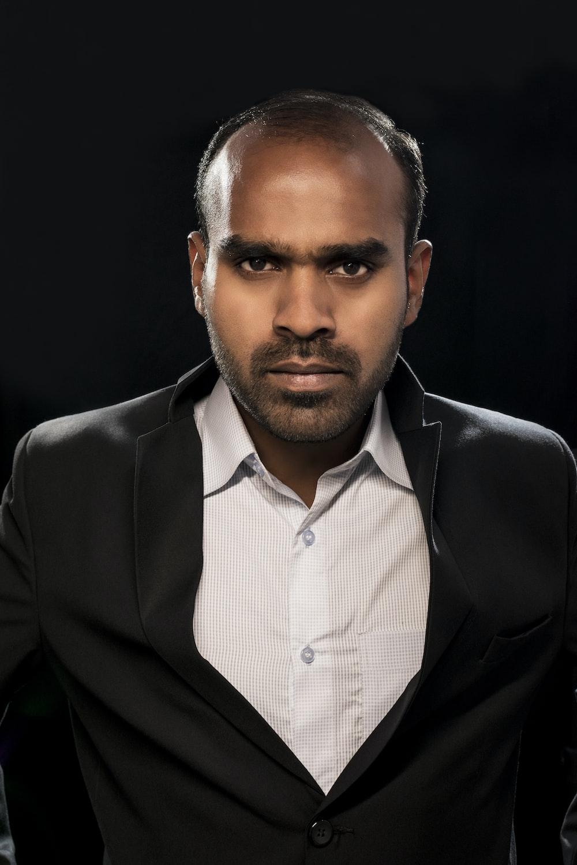 portrait photography of man wearing black notched lapel suit jacket