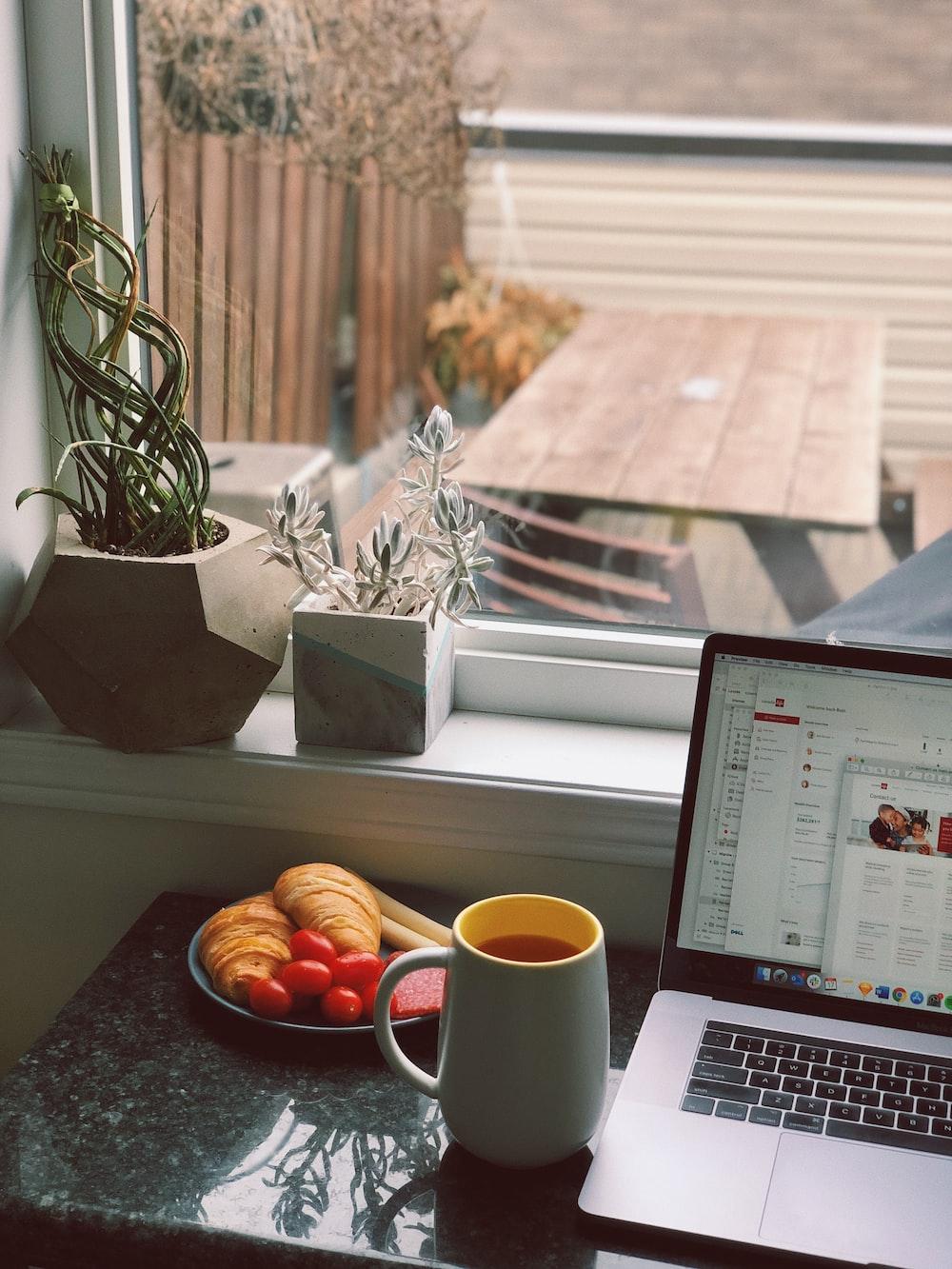 mug beside MacBook