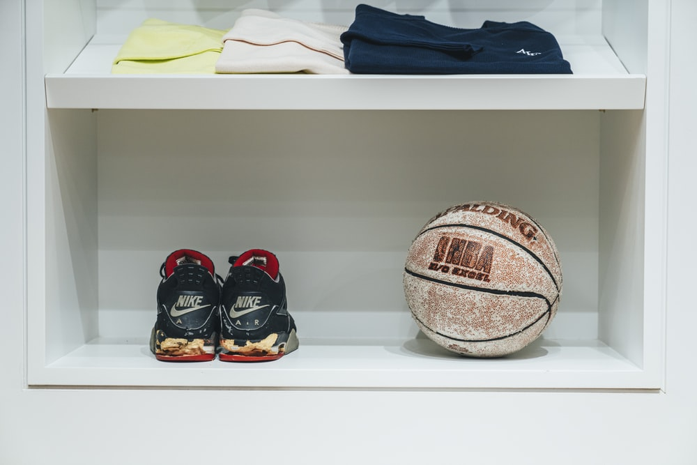 shallow focus photo of pair of black Nike sneakers beside brown basketball
