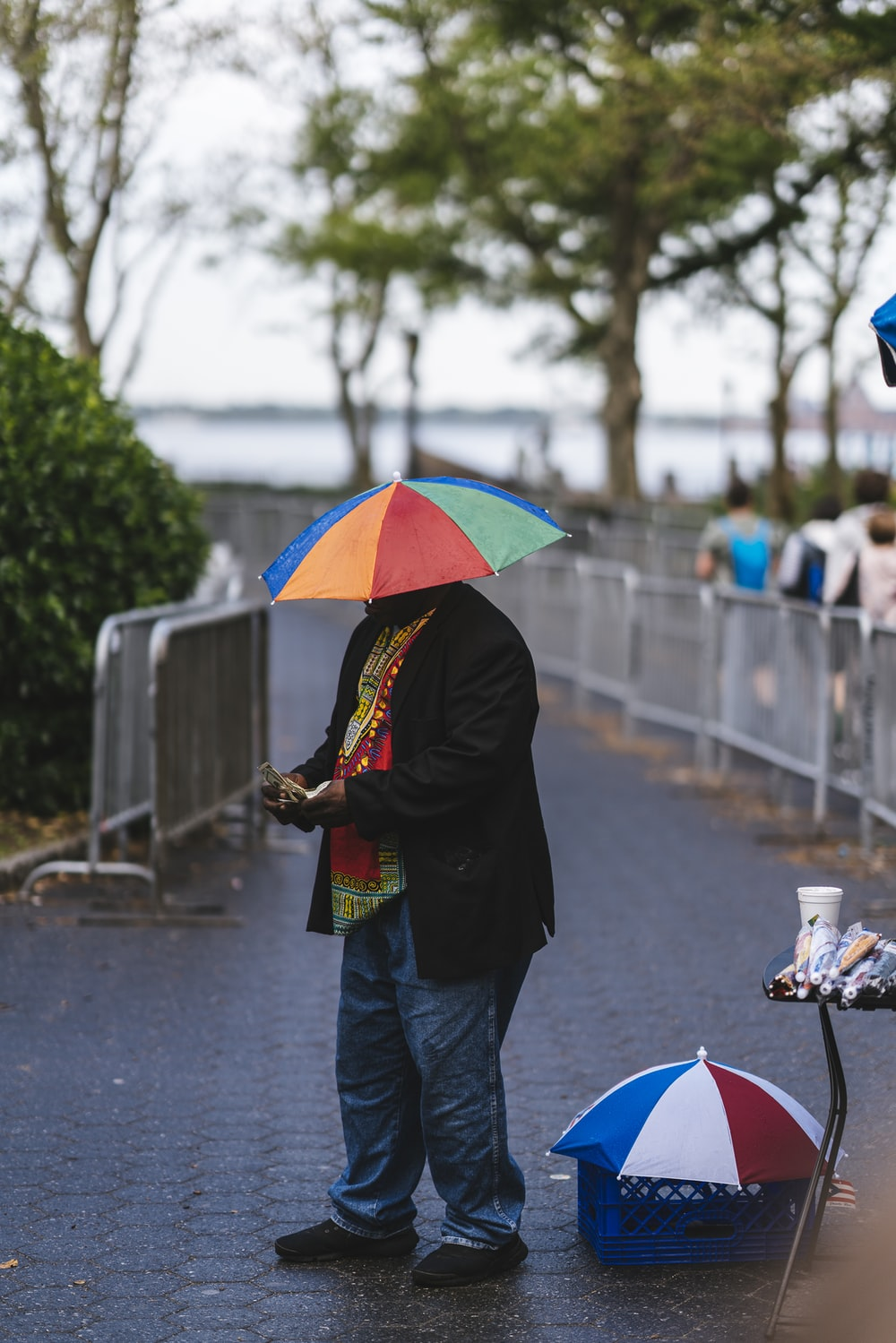 man with multicolored umbrella at standing on pathway and other people walking during daytime
