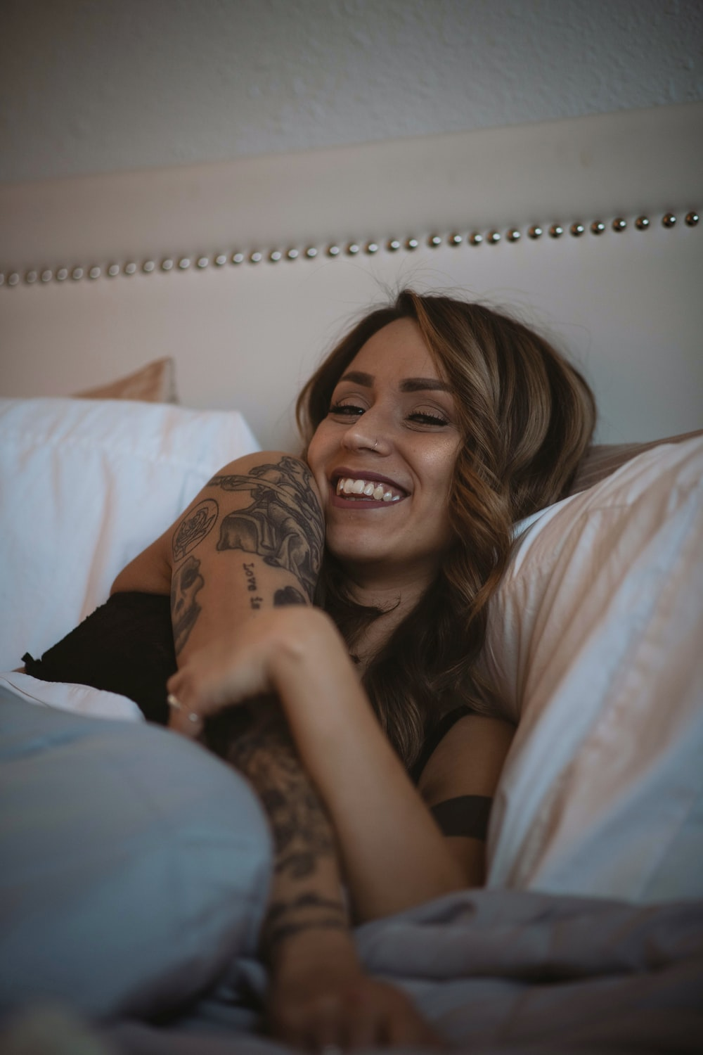 woman wearing black top lying on bed laughing