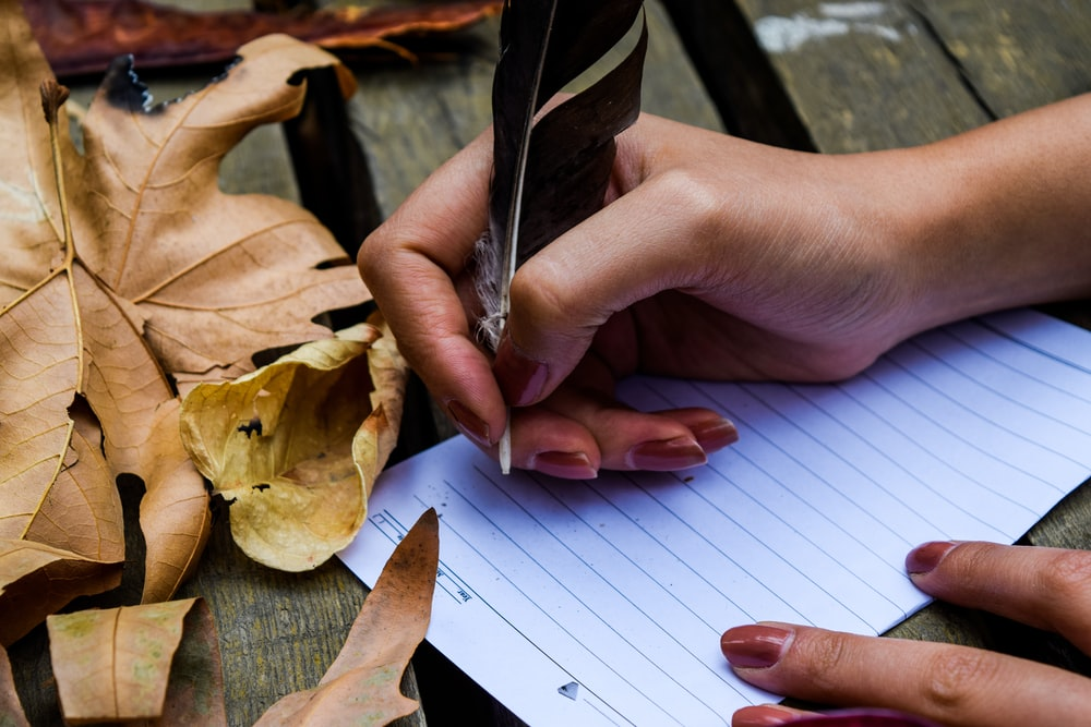 person writing on paper using feather pen