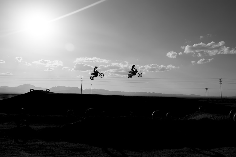 two silhouette of man riding motorcycle