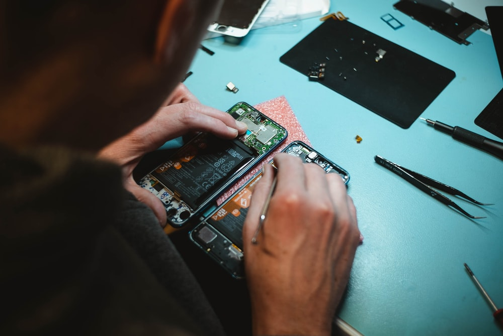 person repairing smartphones under a lighted table