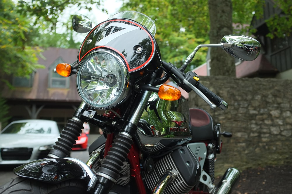 black and red touring motorcycle parking near wall