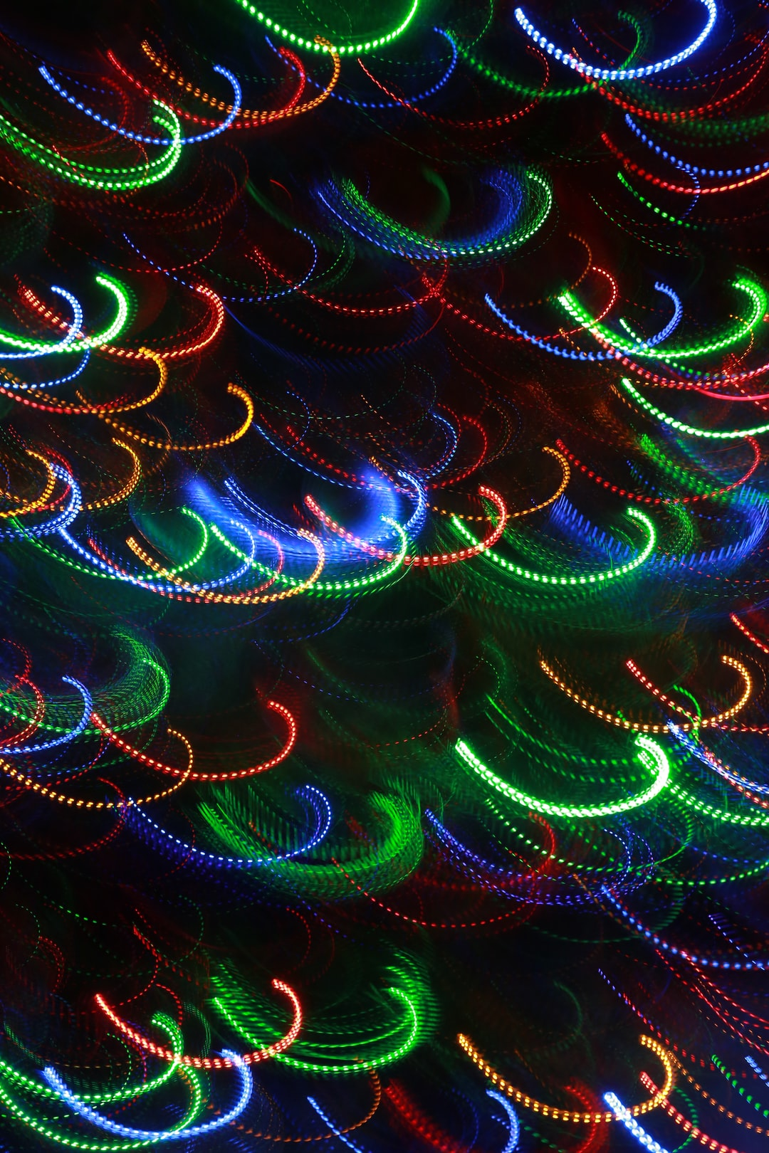 An abstract pattern of half loops in brilliant colors on black background.