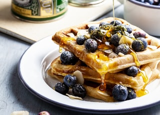 person putting honey on waffle with blueberry fruits