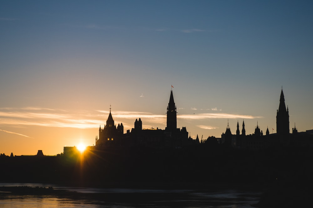 silhouette of houses and tower near river during sunrise
