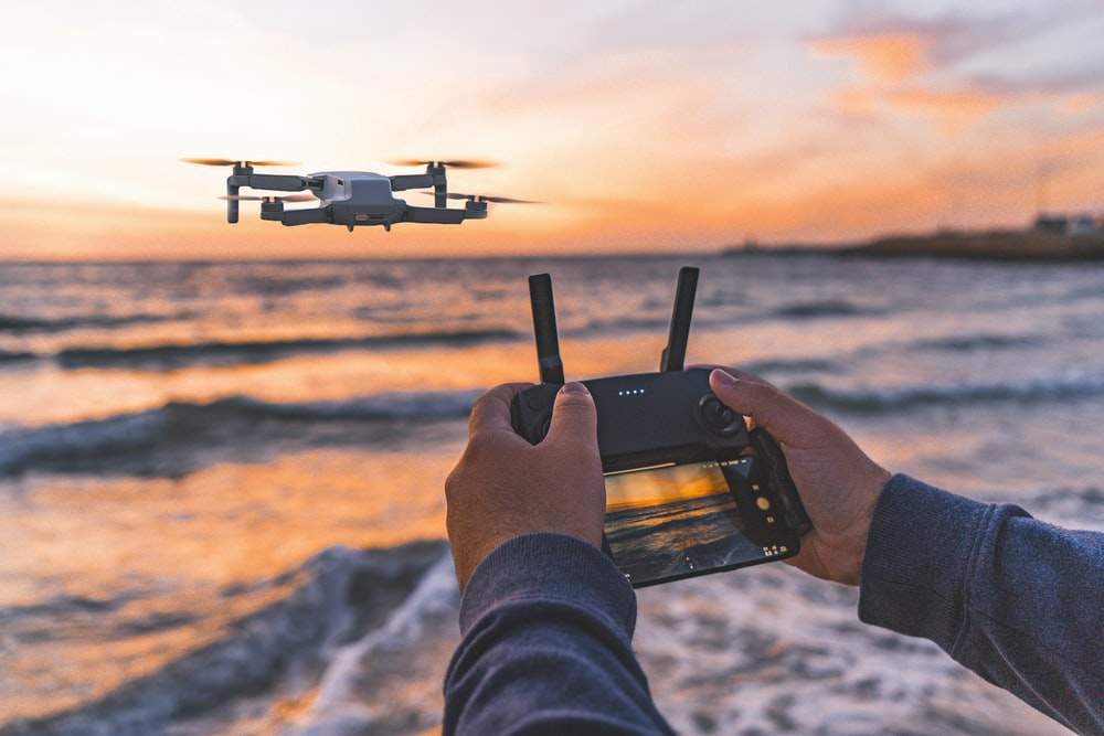 person operating drone flying above seashore