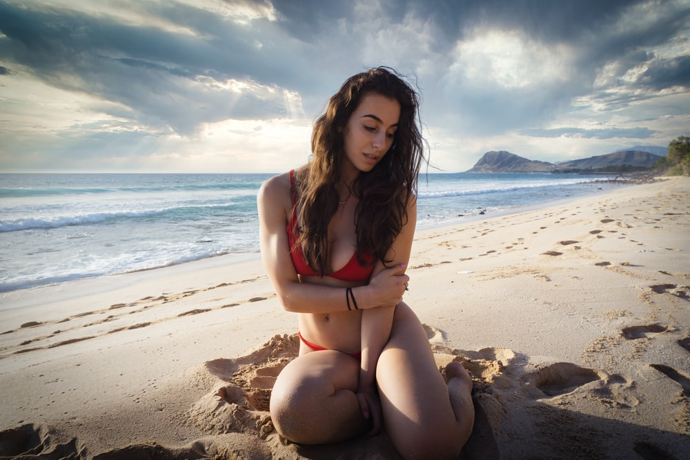 woman wearing bikini while sitting on sand near seashore