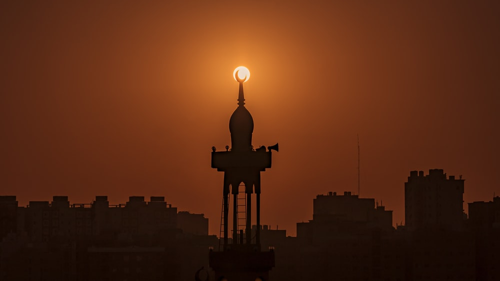 silhouette of mosque near buildings under orange sky