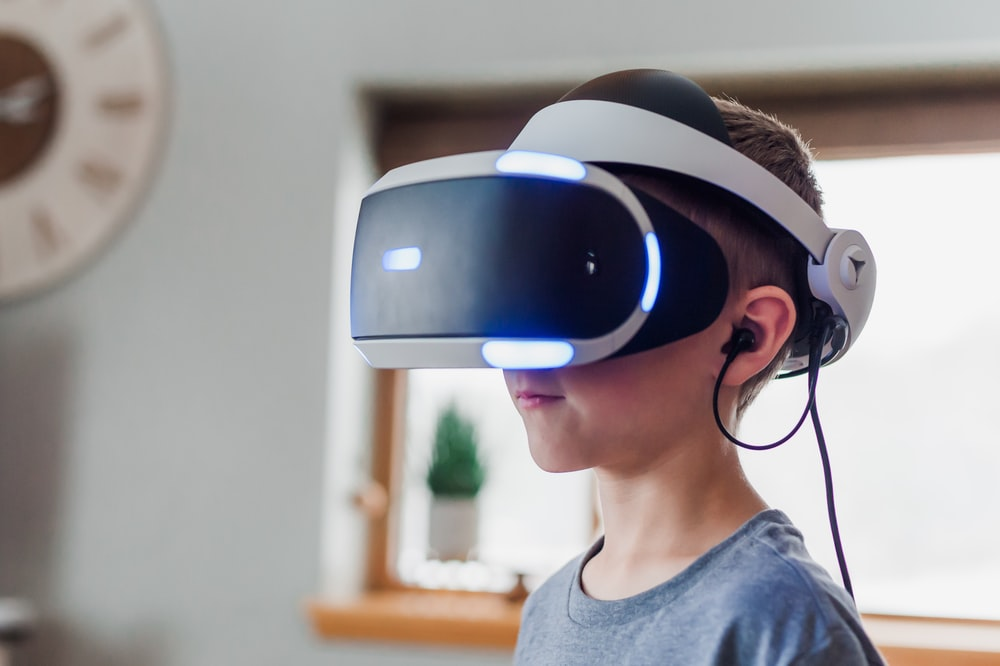 boy wearing black and white VR headset