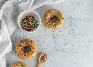 four donuts with sprinkles on top near brown wooden spatula