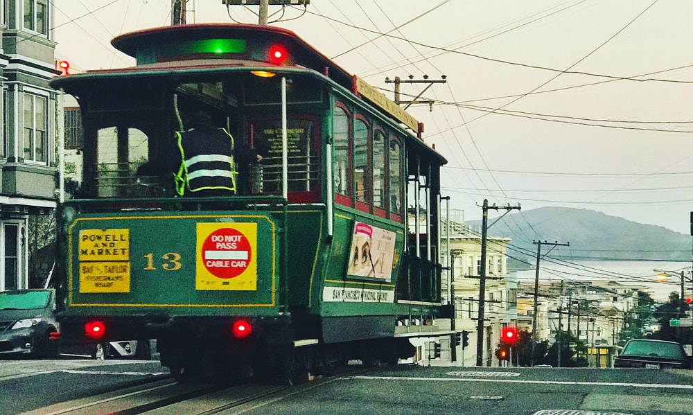 green tram passing by the street