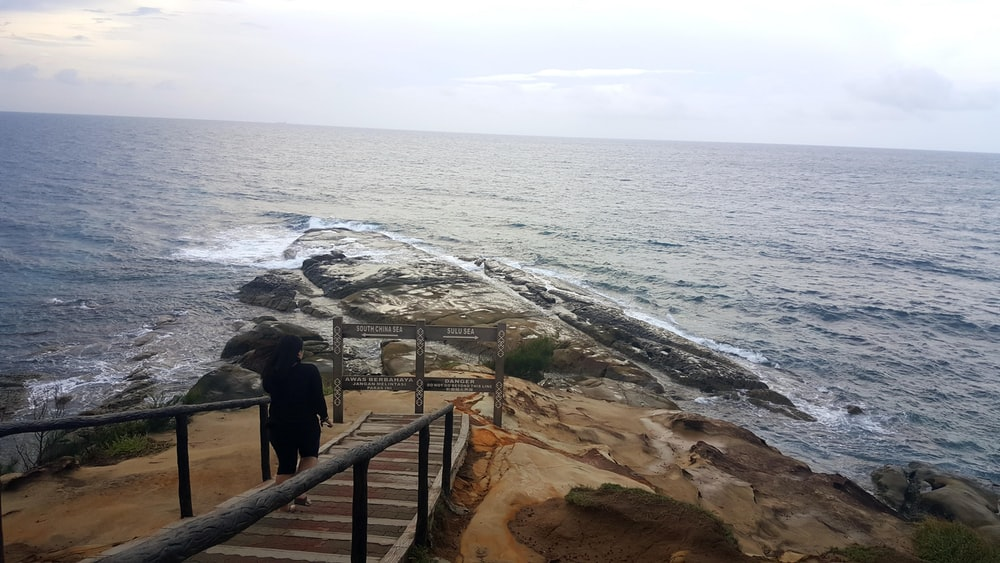 person walking down a stairs leading to the beach