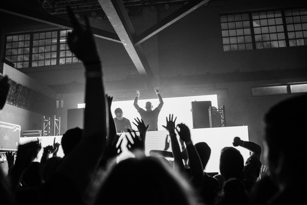 grayscale photography unknown person enjoying on concert