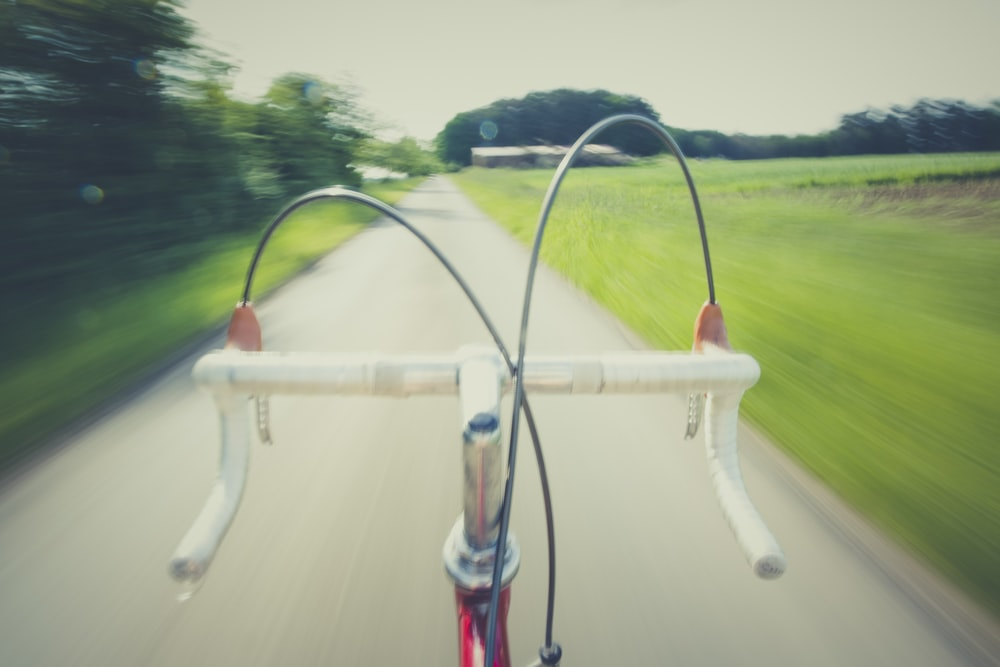 white and red road bike on straight road