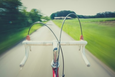 white and red road bike on straight road bow zoom background