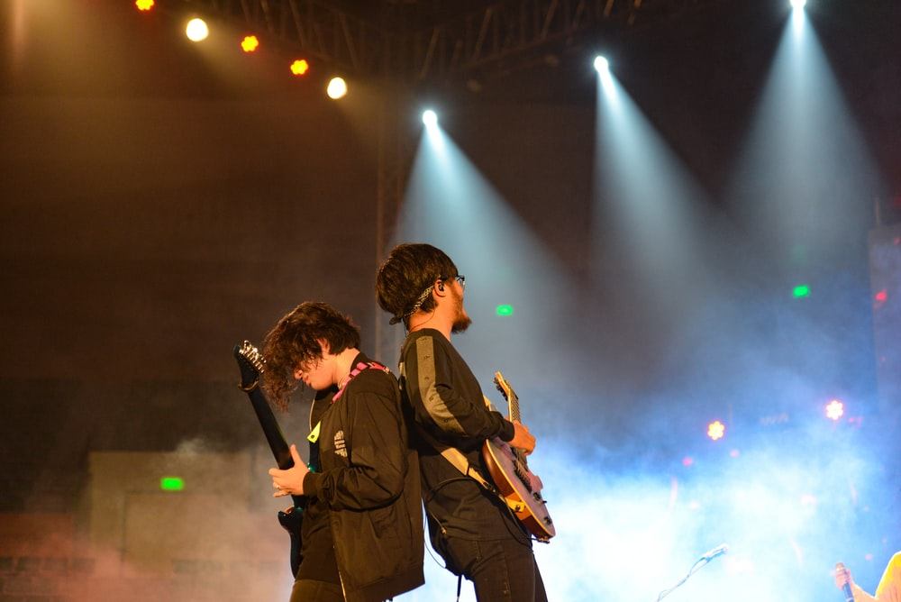 men with guitars on stage