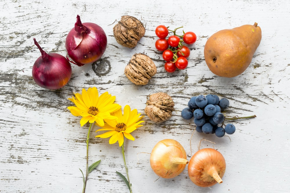 assorted vegetables, fruits, and flowers on white surface