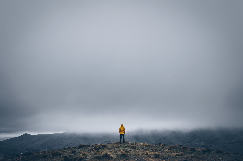 man standing on a mountain cliff under a dramatic sky