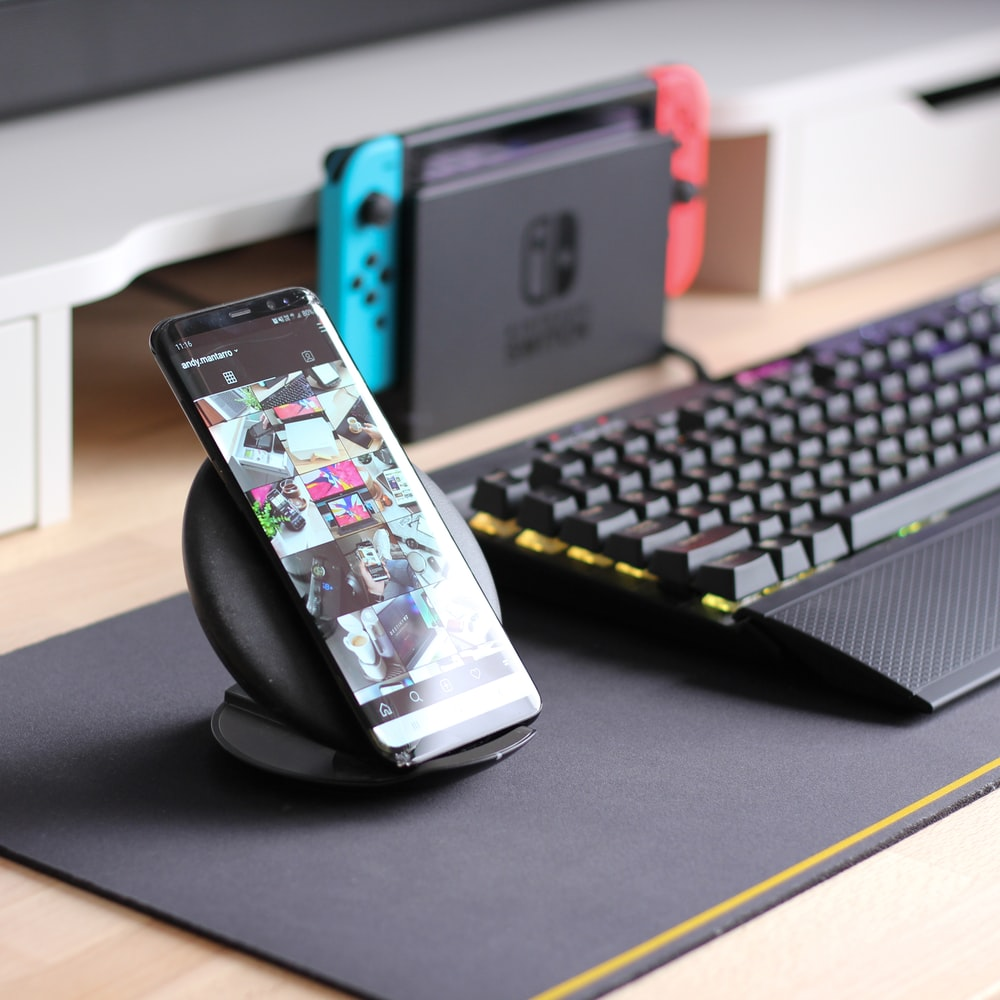 turned-on Android smartphone leaning on stand beside computer keyboard