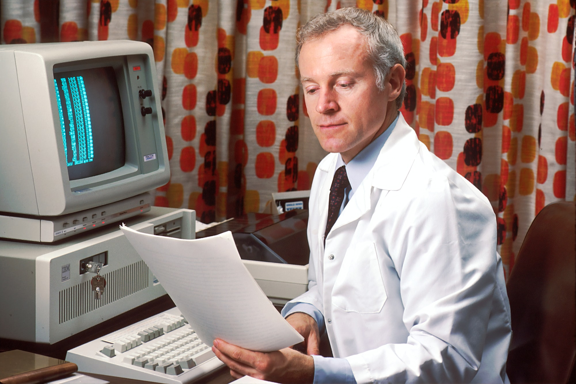 Doctor sitting at his office desk accessing PDQ on his computer in the 1980s. The Physicians Data Query was designed by the National Cancer Institute to help physicians obtain information about the most up-to-date protocols, physicians, and clinics treating cancer patients. 1987