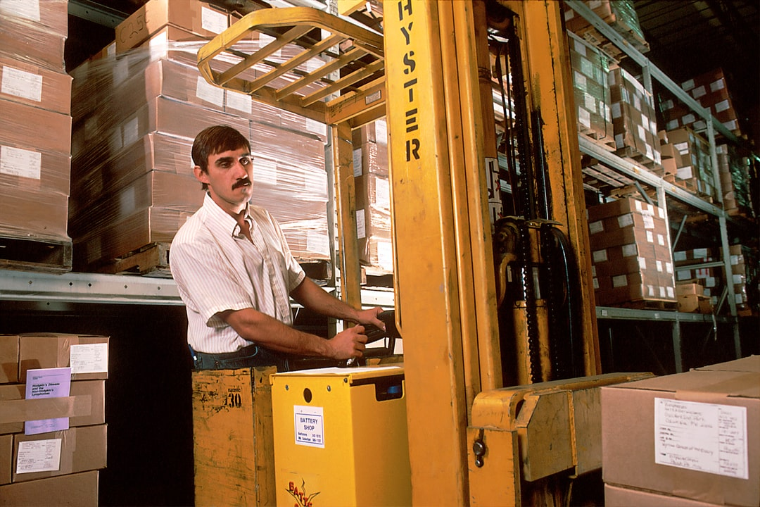 A man driving a fork lift in the warehouse that was once used for the storage and distribution of NCI publications ordered through the NCI Cancer Information Service (CIS). 1988