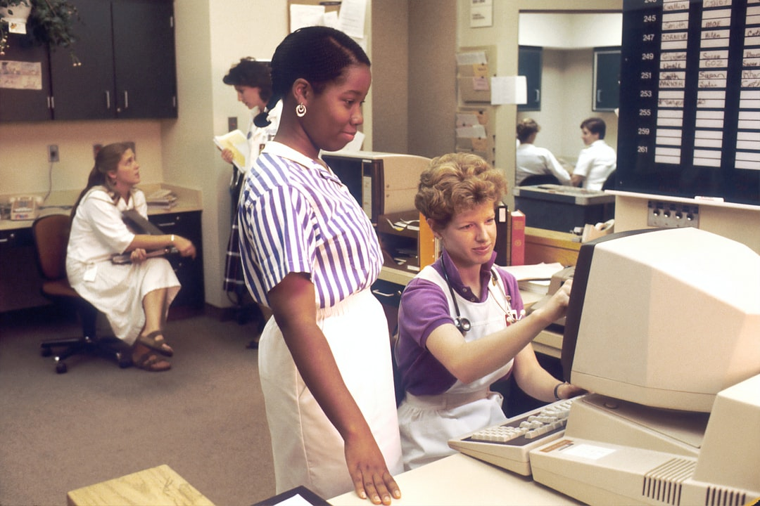 Several nurses in a nurses' station, two of which are working on a computer accessing PDQ. Physicians Data Query was designed by the National Cancer Institute to help physicians and patients obtain information on protocols, physician referrals and clinics using the most up-to-date cancer treatments. 1987
