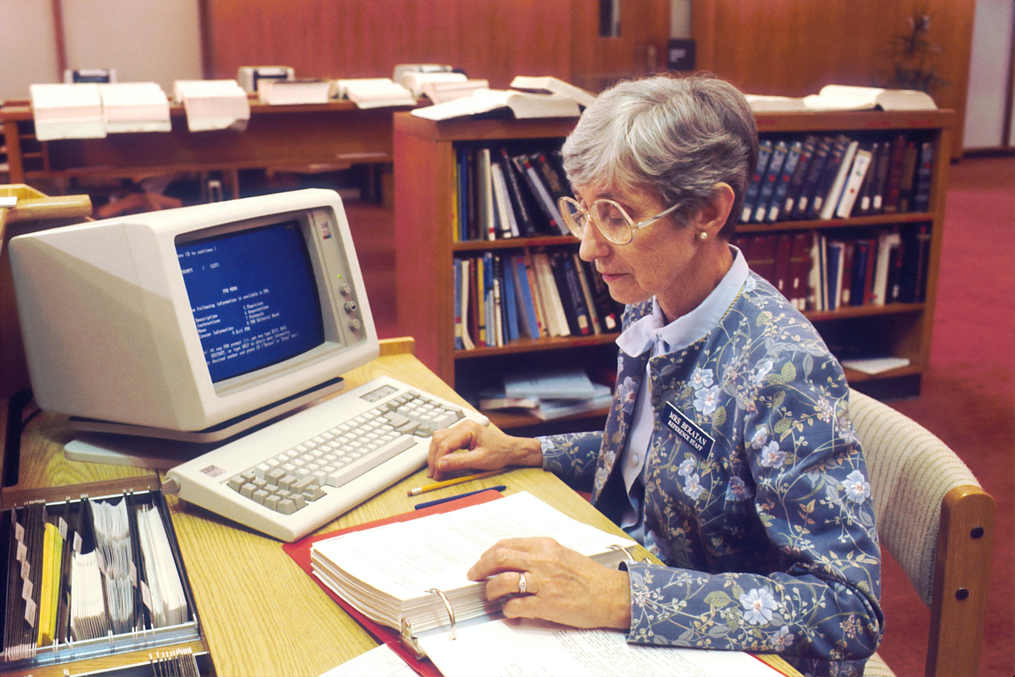 A woman at the National Cancer Institute sitting at a desk with a binder in front of an IBM computer