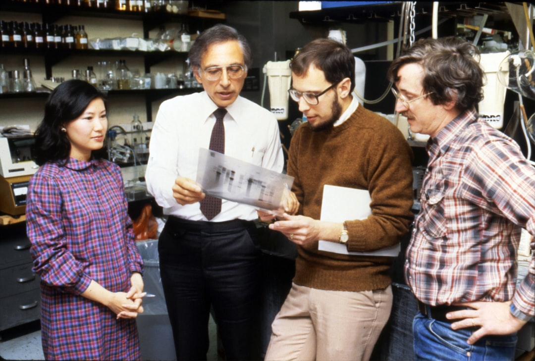 Robert Charles Gallo (second from the left), former Biomedical Researcher. He is best known for his work with the Human Immunodeficiency Virus (HIV), the infectious agent responsible for the Acquired Immune Deficiency Syndrome (AIDS). He was the former Chief of Laboratory of Tumor Cell Biology at the National Institutes of Health. Dr. Gallo is talking with three colleagues (one woman and two men). 1980