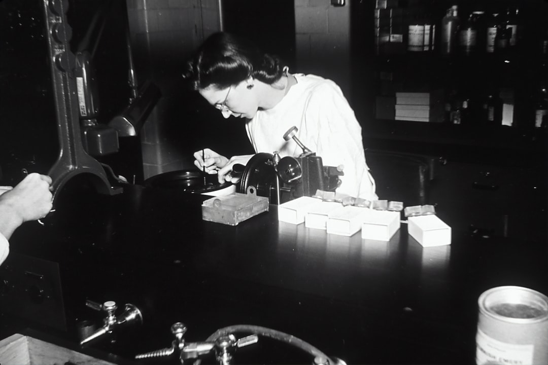 Histology. A Caucasian female creating sections of tissue embedded in paraffin wax are sliced and floated on a hot-water bath in preparation for histological study. 1950.