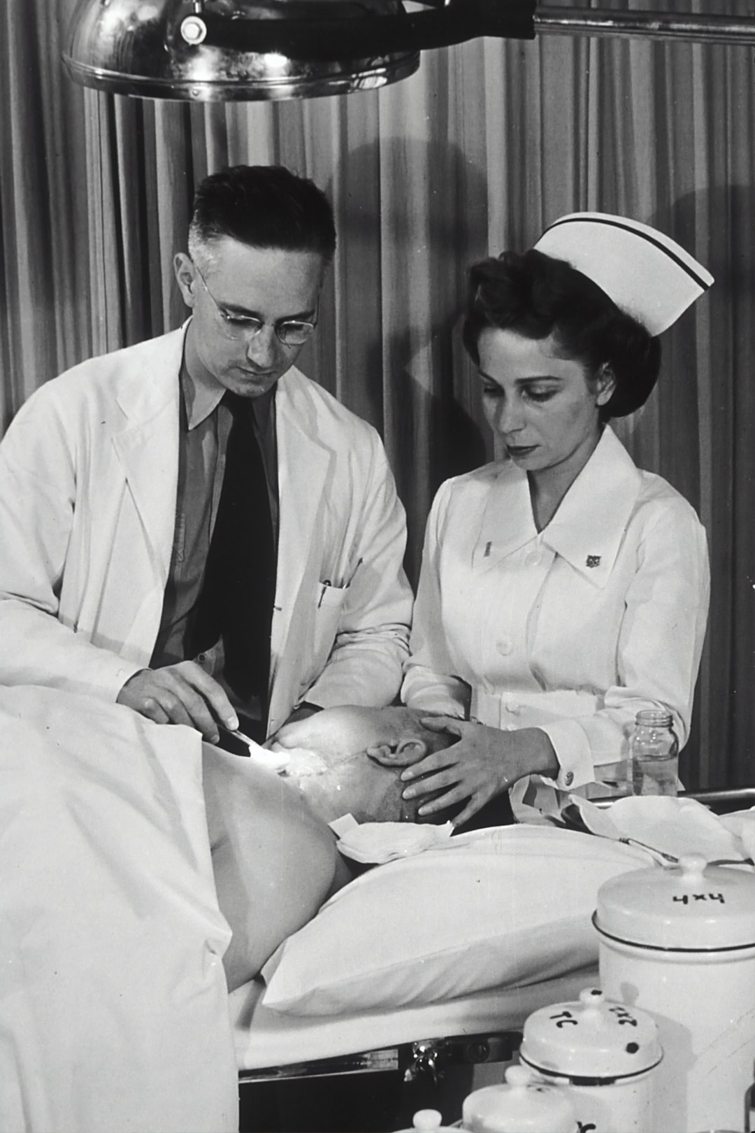 A Caucasian physician is changing the dressing on a patient's neck, while a Caucasian nurse holds the patient's head. Photo was taken at Public Health Service Tumor Clinic, Marine Hospital, Baltimore. 1950