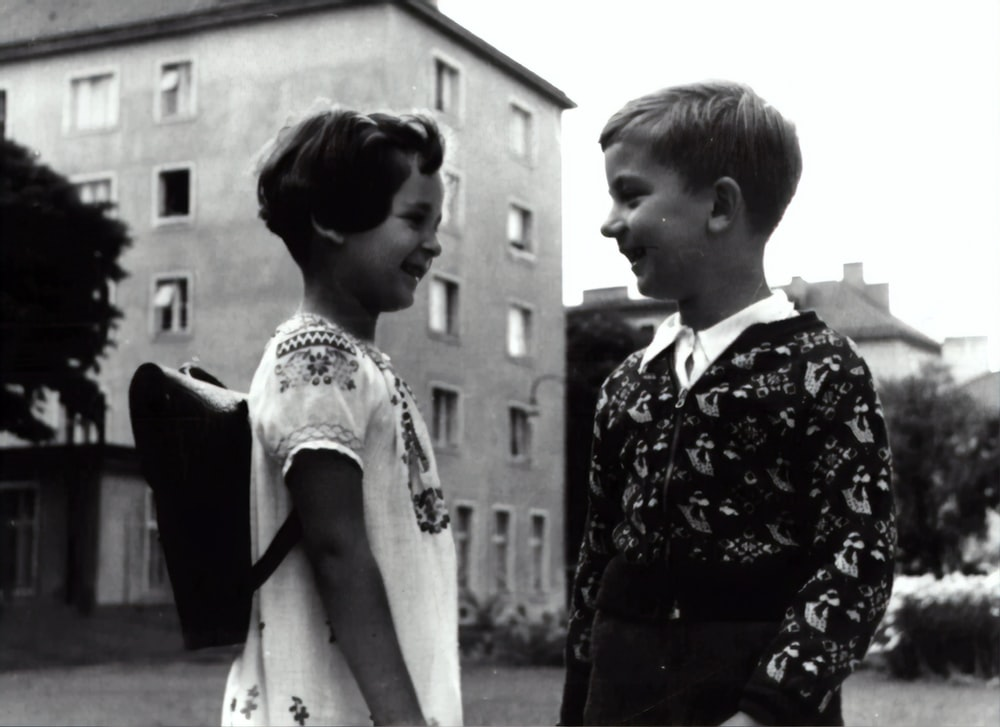 grayscale photography of boy and girl facing each other