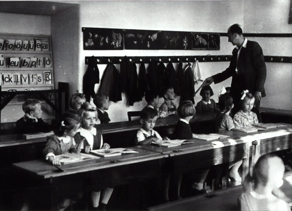 grayscale photography of children sitting inside room