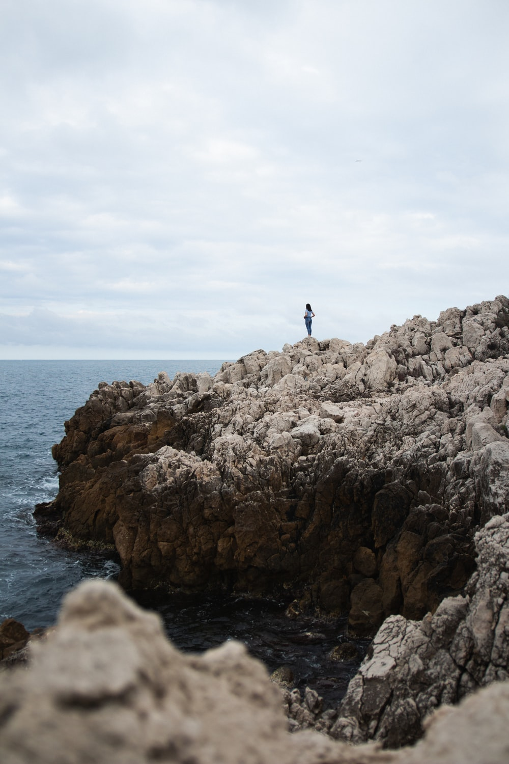 shallow focus photo of person standing on cliff during daytrime