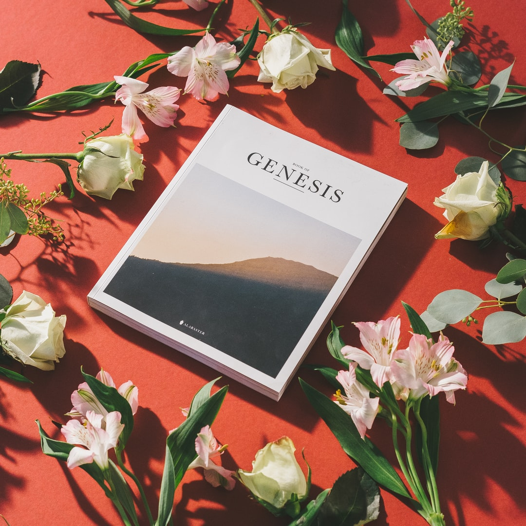 Book of Genesis with flowers on a red background