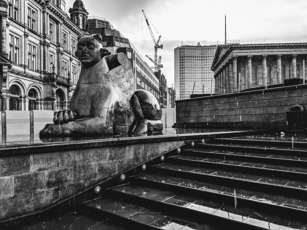 grayscale photography of sphinx statue and stairs