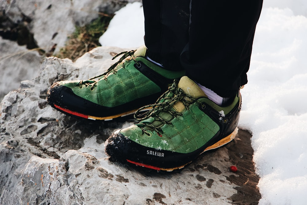 person in green-black low-top sneakers standing on top of rock