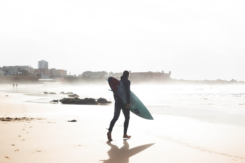 man carrying surfboard while walking towards the sea