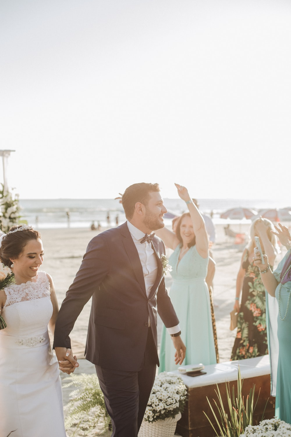 newly wed couple holding hands while standing surrounded with people viewing sea during daytime